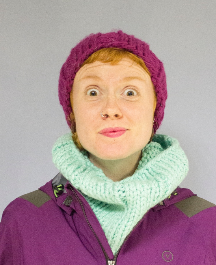 Amused face wearing On The Glo purple beanie and mint snood